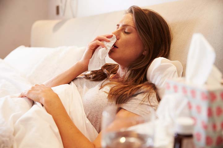 Woman suffering from cold lying in bed - how to obtain a fit note